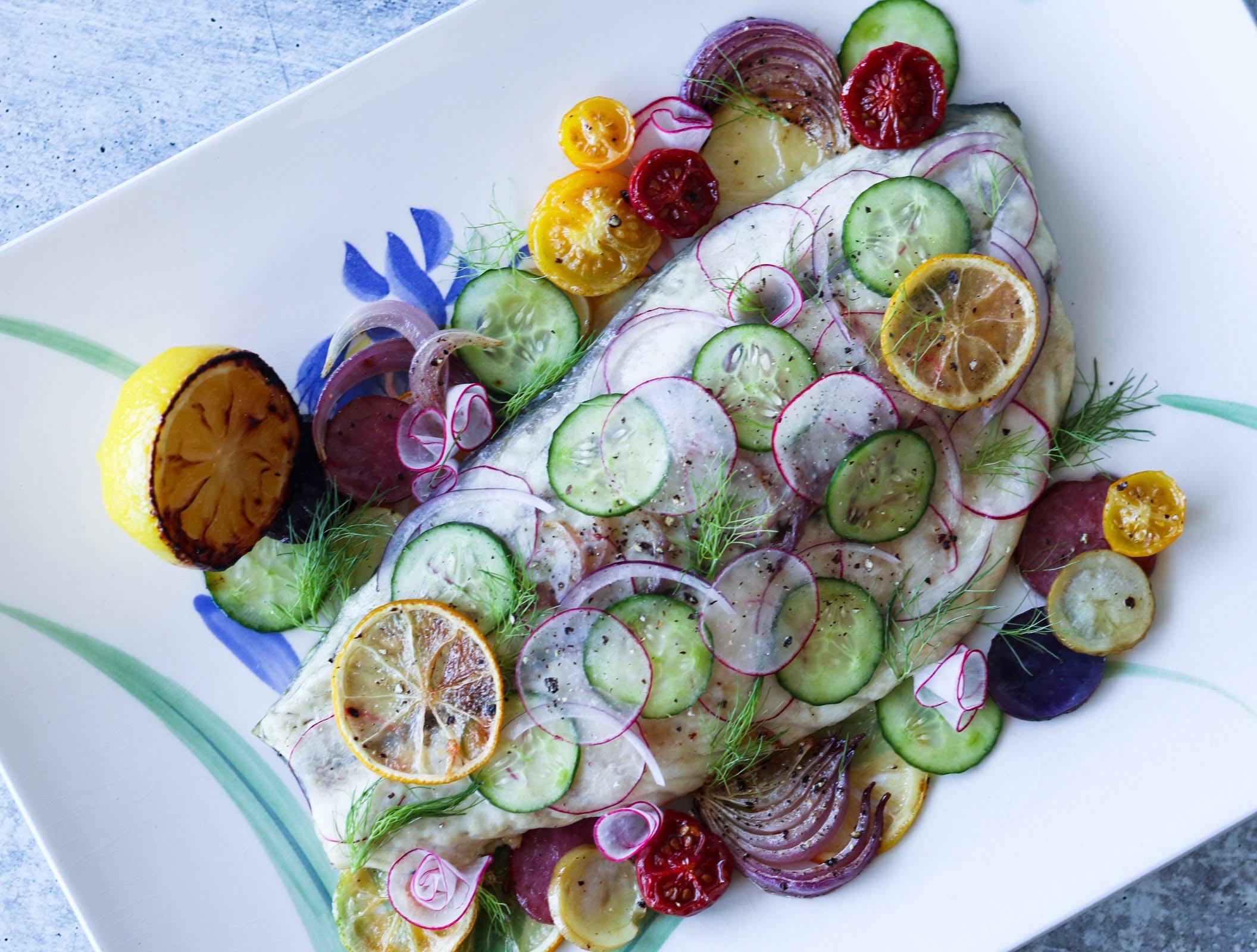 Barramundi with roasted fingerling potatoes, cherry tomatoes, red onions, cucumbers, radishes, lemons, fennel